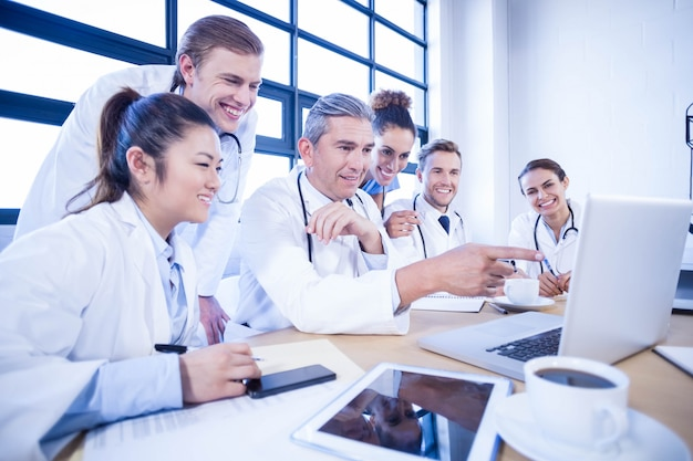 Gruppo di medici che esamina computer portatile e che ha una discussione all'auditorium