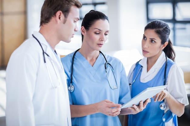 Gruppo di medici che esamina il pc della compressa nel corridoio