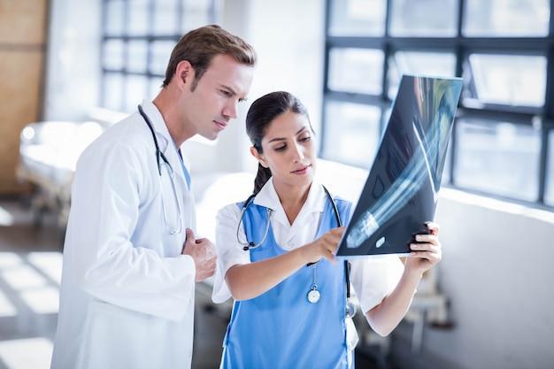 Gruppo di medici che esamina insieme raggi x all'ospedale