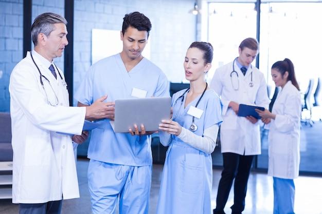 Gruppo di medici che esamina referto medico e che utilizza computer portatile e compressa digitale nell'ospedale