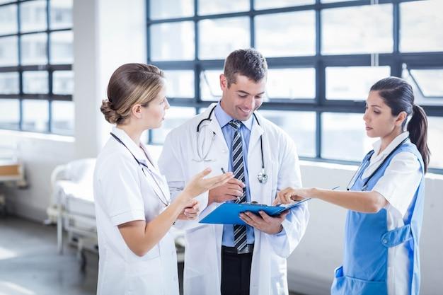 Gruppo di medici che sta e che parla all'ospedale