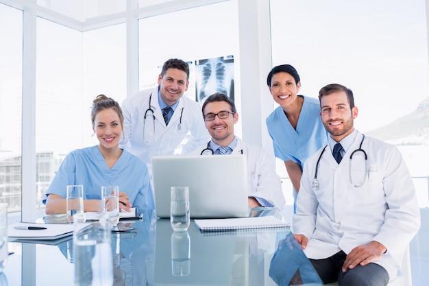 Gruppo di medici felice che per mezzo insieme del computer portatile