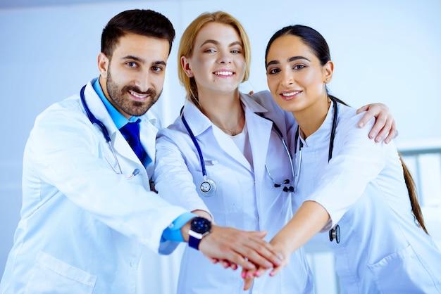 Gruppo di medici multirazziale che impila le mani in ospedale