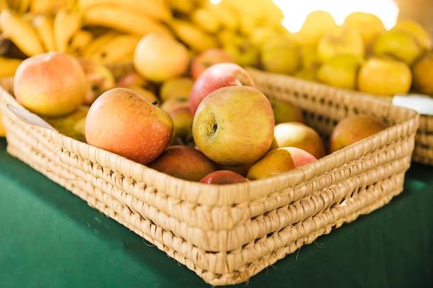 Gruppo di mele nel cesto di vimini sul tavolo al mercato della frutta