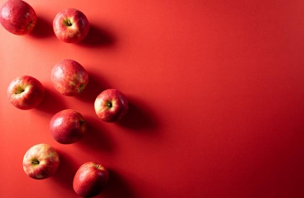 Gruppo di mele rosse su carta rossa