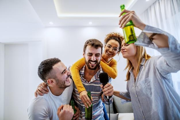 Gruppo di migliori amici che si divertono a casa. bevono birra e organizzano serate di karaoke.