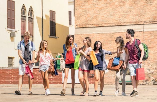 Gruppo di migliori amici felici con i sacchetti della spesa che camminano nel centro urbano