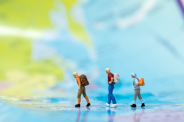 Gruppo di mini figure miniatura viaggiatore con zaino a piedi sulla mappa del mondo.