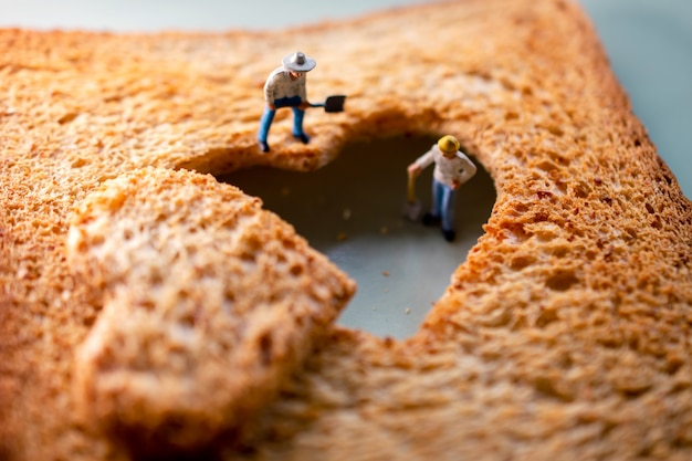 Gruppo di miniatura dell'operaio che ripara un pane tostato affettato bruciato a forma di cuore