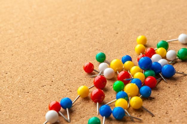 Gruppo di perni di spinta colorati sulla bacheca di sughero