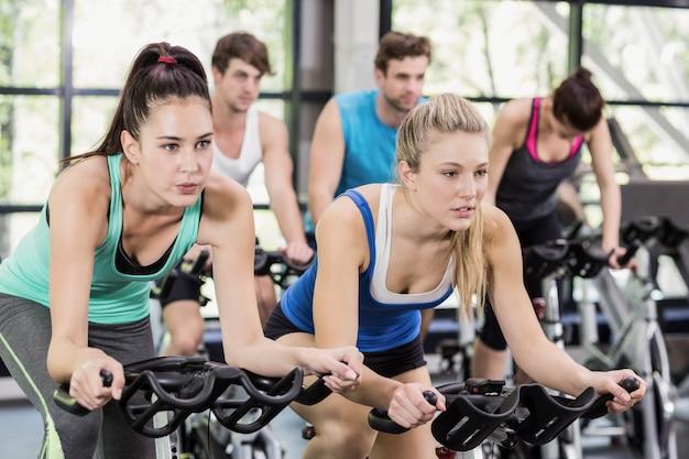 Gruppo di persone adatto facendo uso della bici di esercizio insieme alla palestra
