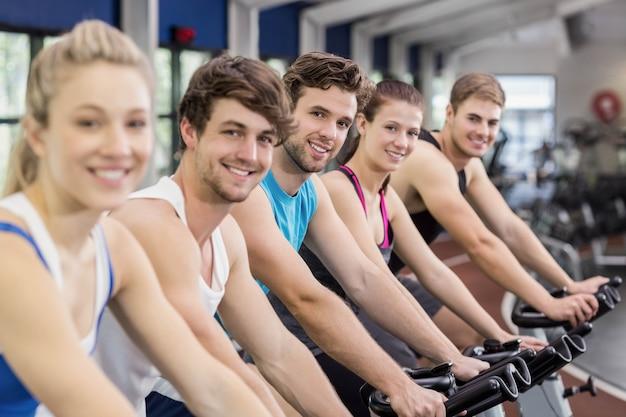 Gruppo di persone adatto facendo uso della bici di esercizio insieme in palestra