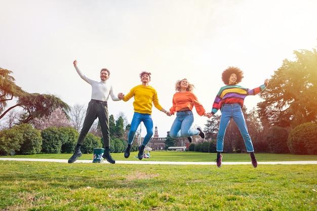 Gruppo di persone amici saltando la retroilluminazione esterna