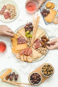 Gruppo di persone che condividono un cheeseboard e salsicce in un brunch di celebrazione. concetto di cibo