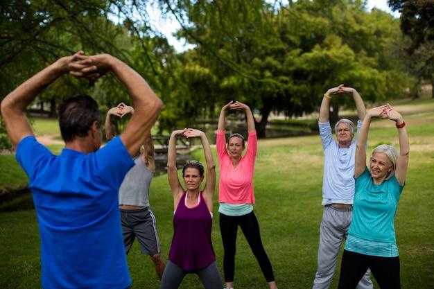 Gruppo di persone che eseguono allungando esercizio