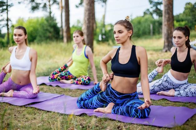 Gruppo di persone che fanno yoga sul verde con erba fresca all'aperto. uno stile di vita sano