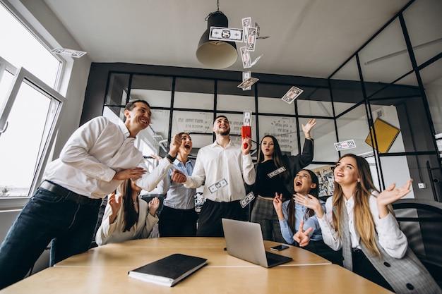 Gruppo di persone che gettano soldi in un ufficio