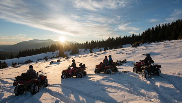 Gruppo di persone che godono del tramonto su quad bike sulla neve in montagna in inverno