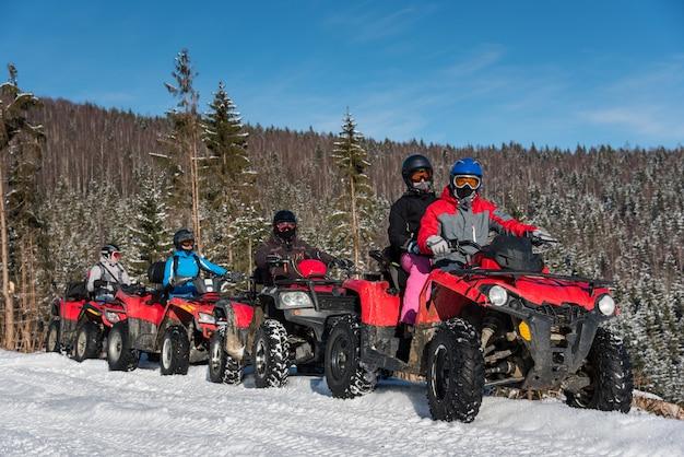 Gruppo di persone che guidano le atv a quattro ruote su neve in inverno