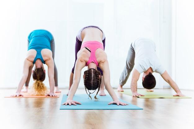 Gruppo di persone che praticano yoga a casa. adho mukha svanasana posa.
