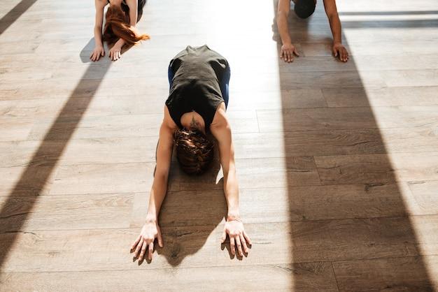 Gruppo di persone che praticano yoga sul pavimento di legno in studio