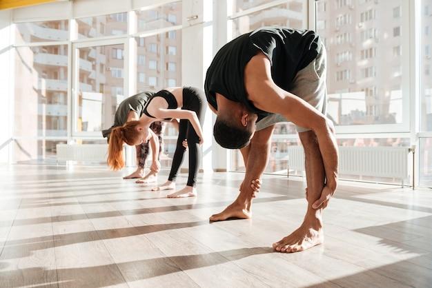 Gruppo di persone che stanno e che si scaldano facendo uso della posa di yoga