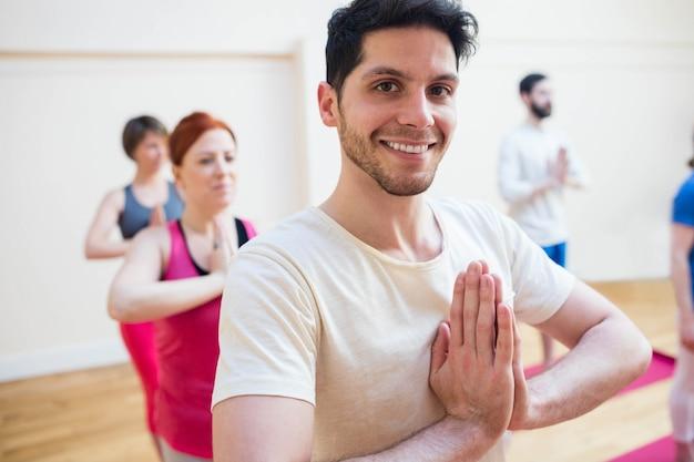 Gruppo di persone che svolgono esercizio yoga albero posa