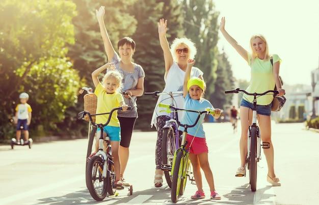 Gruppo di persone che uniscono le loro mani mentre tengono le loro biciclette