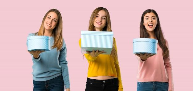 Gruppo di persone con abiti colorati in possesso di un dono in mano su sfondo colorato