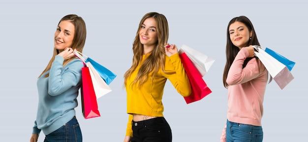 Gruppo di persone con i vestiti variopinti che tengono molti sacchetti della spesa su fondo variopinto