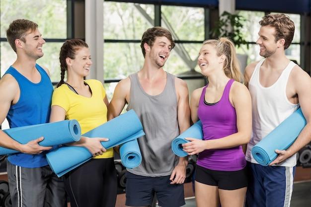 Gruppo di persone con tappetino fitness in palestra