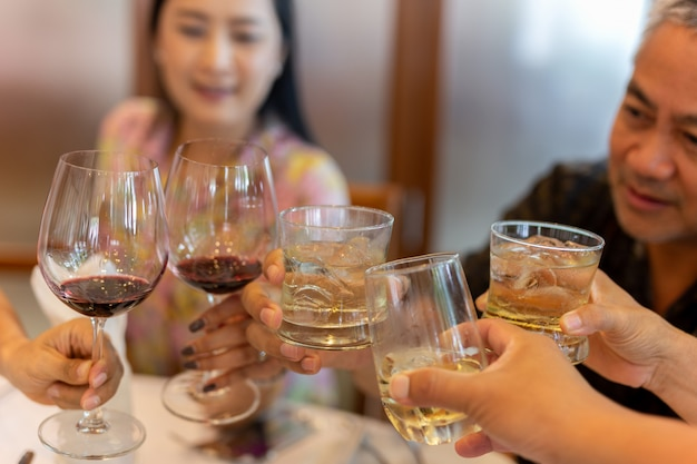 Gruppo di persone con vino rosso e wishkey facendo un brindisi al successo festa celebrazione