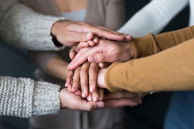 Gruppo di persone del primo piano che tengono le mani