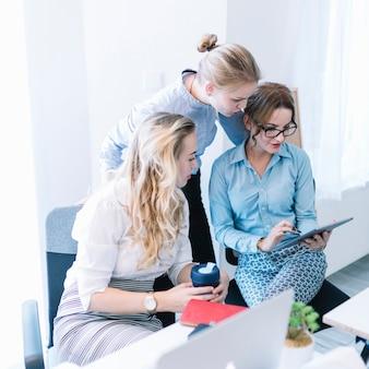 Gruppo di persone di affari che esaminano compressa digitale nella riunione dell'ufficio