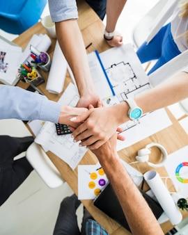 Gruppo di persone di affari che impilano le loro mani sopra la scrivania in legno