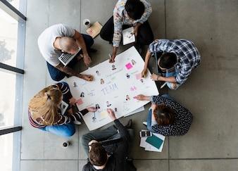 Gruppo di persone di brainstorming seduti sul pavimento