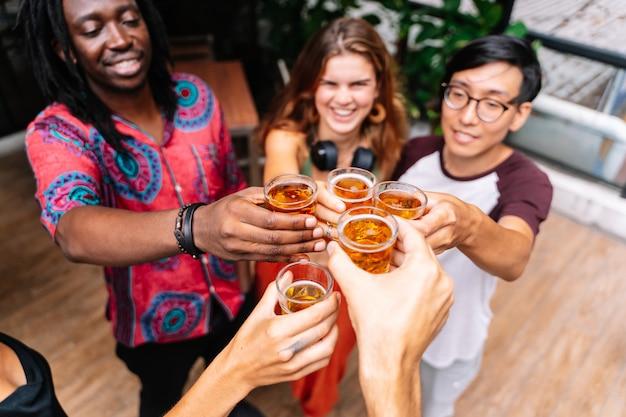 Gruppo di persone di diverse etnie che tostano con la birra