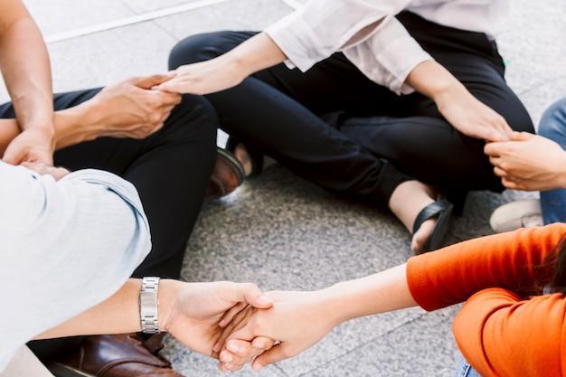 Gruppo di persone di lavoro di squadra che si tengono per mano insieme