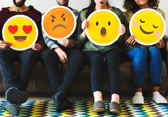 Gruppo di persone diverse che tiene icone emoticon