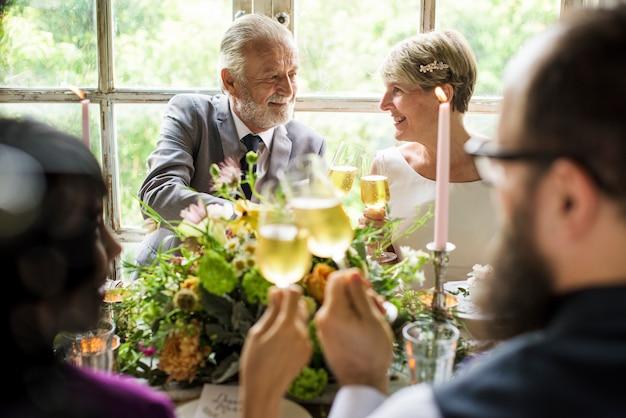 Gruppo di persone diverse tintinnio di bicchieri di vino insieme
