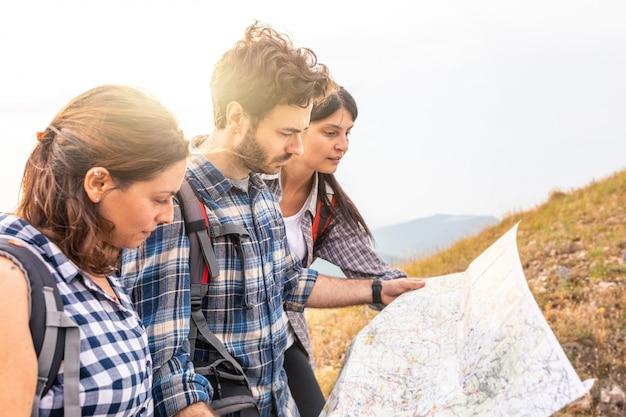 Gruppo di persone escursioni e guardando la mappa durante la loro avventura