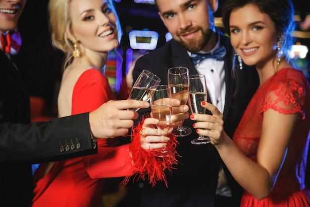 Gruppo di persone felici che bevono vino spumante nel casinò