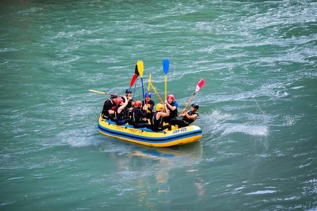 Gruppo di persone felici con guida rafting e canottaggio sul fiume.
