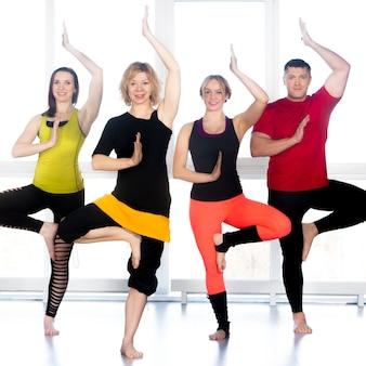 Gruppo di persone felici in piedi in yoga asana in classe