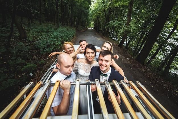 Gruppo di persone in auto che festeggiano il matrimonio