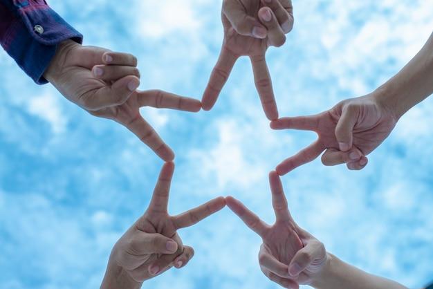 Gruppo di persone in cinque persone che usano le dita per formare una stella con il cielo blu.