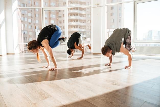 Gruppo di persone in equilibrio sulle mani e praticare yoga