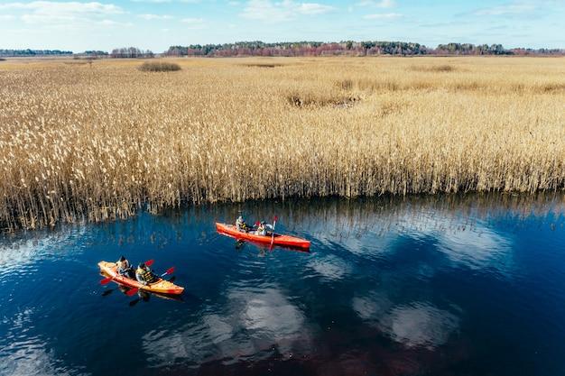 Gruppo di persone in kayak tra le canne sul fiume in autunno.
