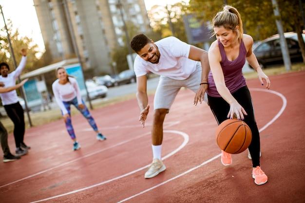Gruppo di persone multietniche che giocano a basket in campo