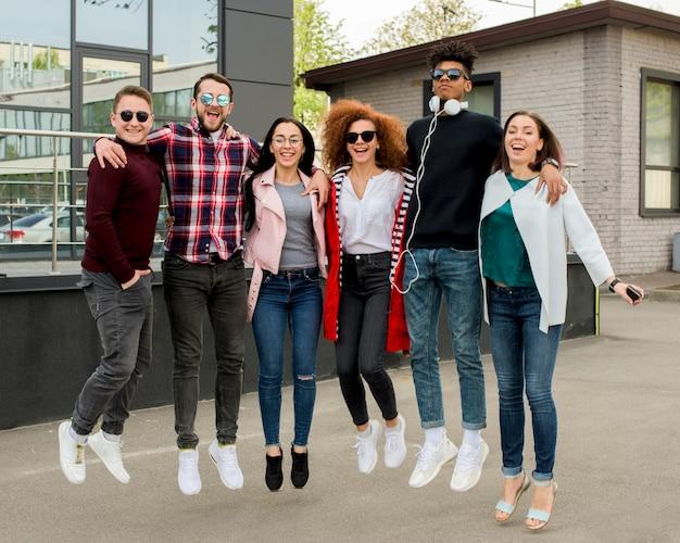 Gruppo di persone multirazziale allegro che saltano insieme sulla via